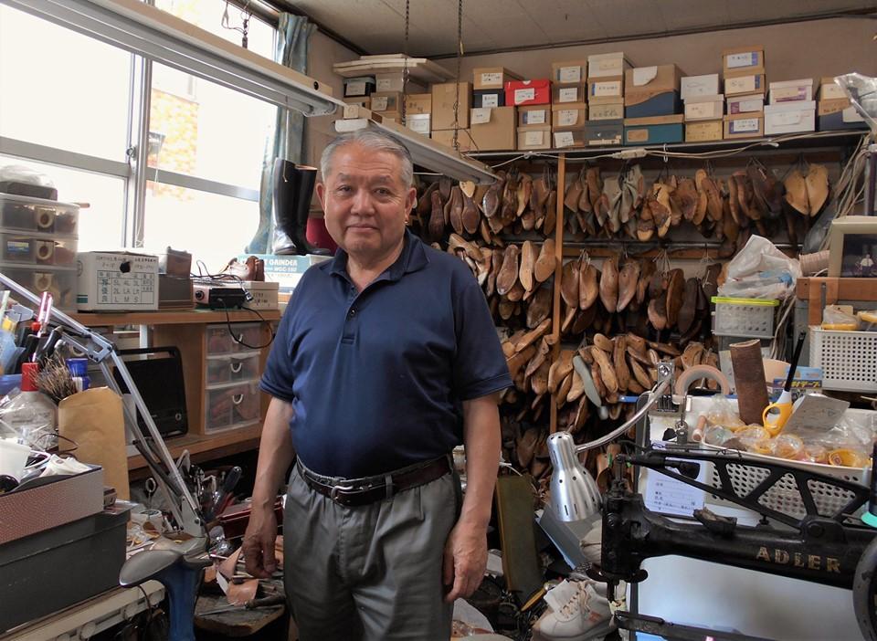 仕事場に立つ小澤さん。後ろにはたくさんの木型があります。
