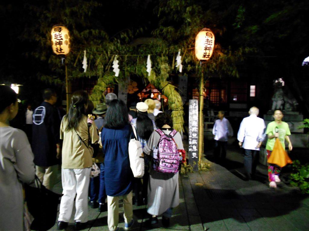 鳥越神社で茅の輪をくぐる人たちの画像。