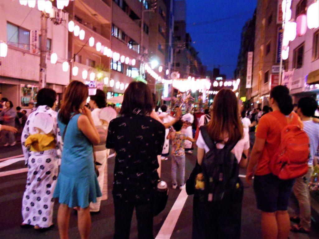 盆踊りする人たちと、それを眺める外国人旅行客の女性4人。