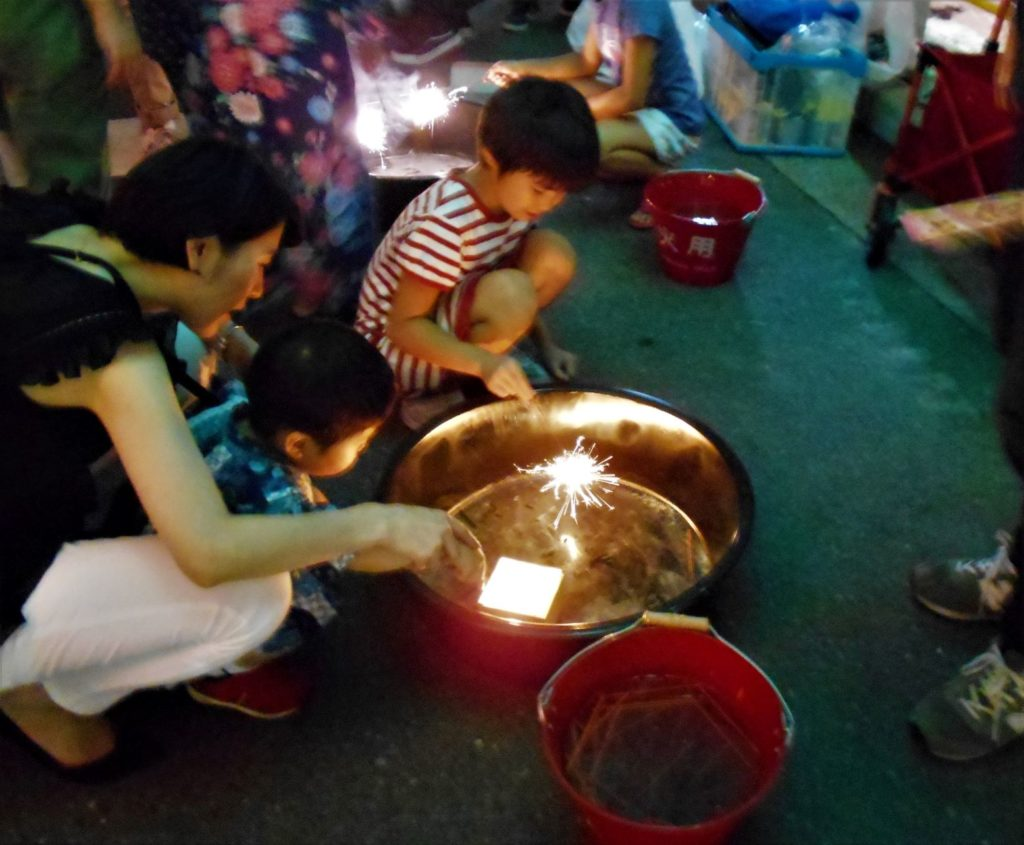 花火ブースで手持ち花火を楽しむ子供たち。
