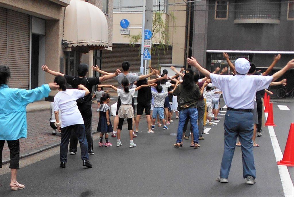 道路でラジオ体操する画像。