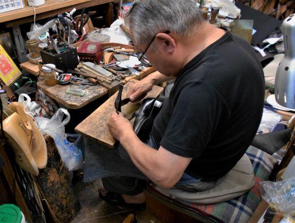 尾錠に穴をあけて靴を仕上げる画像。