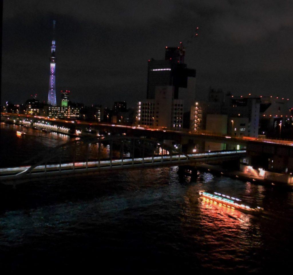夜の隅田川を遡上する屋形船の列の画像。