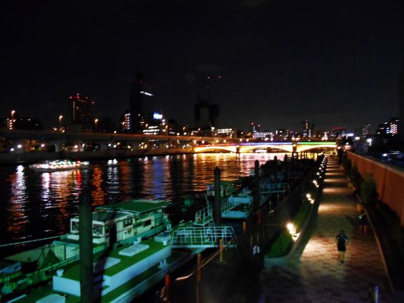 ライトアップされた橋梁群をつなぐ隅田川テラスにはジョギングや散策を楽しむ人々の画像