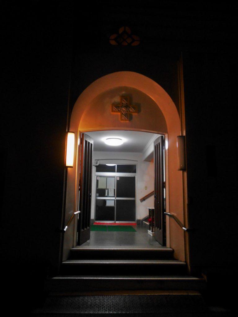 灯りのともる教会の入り口の画像.