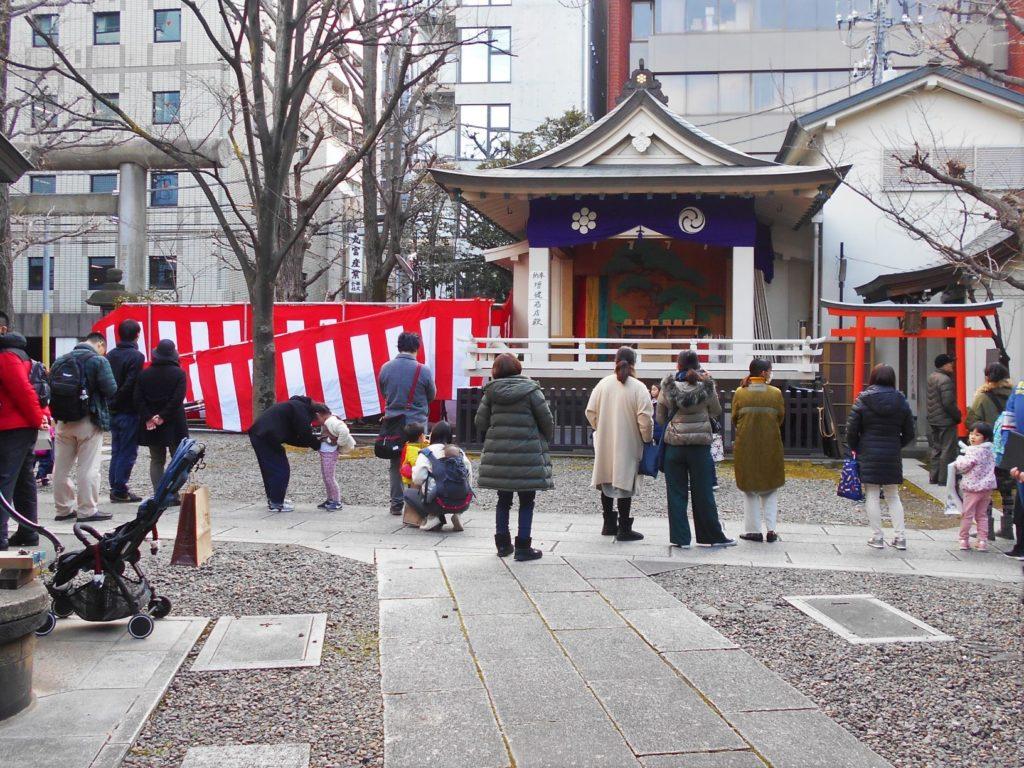 榊神社で豆まきを待つ親子連れの画像