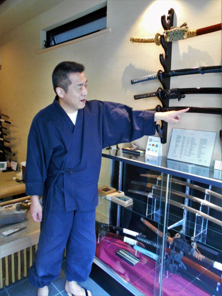 工房内の日本刀を使って刀の魅力を教えてくれる長岡先生の画像。