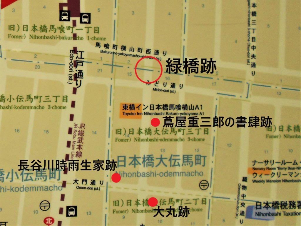 住所表示版に緑橋、蔦屋重三郎の書肆、大丸、長谷川時雨生家のそれぞれの跡地を記した地図の画像。